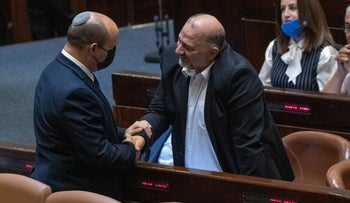 Prime Minister Naftali Bennett shakes hands with Mansour Abbas in the Knesset, in June.