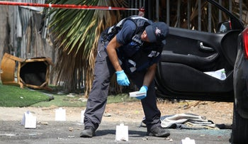 A policeman collects evidence after a murder in Lod, last month.
