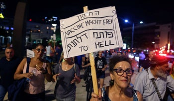A woman at a Tel Aviv rally protesting government pandemic restrictions. Her sign in a mix of Hebrew and English reads: 'The vaccine opens doors to hell.'