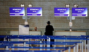 An ultra-Orthodox Jewish man stands at an El Al check-in counter at Ben Gurion International airport, Israel.