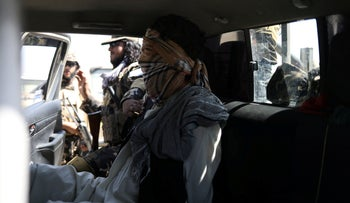 A suspected ISIS member sits blindfolded in a Taliban Special Forces' car in Kabul.