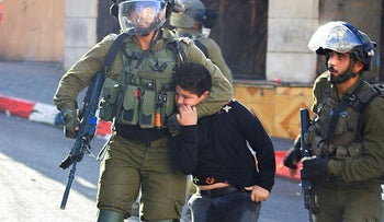 Israeli soldiers detain a Palestinian boy during clashes in Hebron, West Bank, last week.