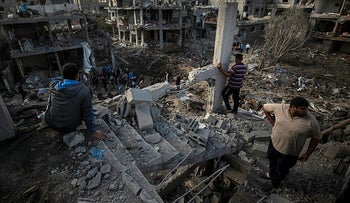 Palestinians inspect their destroyed houses following overnight Israeli airstrikes in town of Beit Hanoun, Gaza, May 2021.