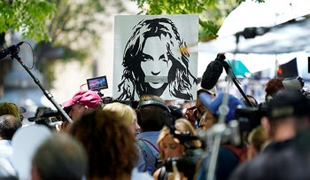 A portrait of Britney Spears looms over supporters and media outside a court hearing concerning her conservatorship at the Stanley Mosk Courthouse in Los Angeles.