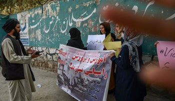 A Taliban member remonstrates with protestors outside a school in Kabul this week calling for education and equal rights for women, as another Taliban tries to block the camera with his hand.