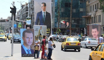 People stand near posters depicting Syria's President Bashar al-Assad, ahead of the presidential election, in Damascus, Syria, in May.