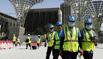 Technicians walk at the three thematic districts at the under construction site of the Expo 2020 in Dubai, United Arab Emirates