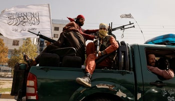 Members of Taliban forces ride on a pick-up truck mounted with a weapon in Kabul, Afghanistan, on Sunday.