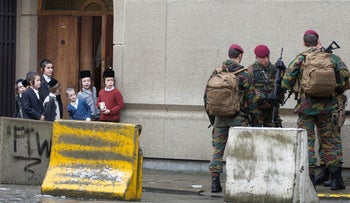 Jewish children look at Belgian soldiers as they patrol during religious services in Antwerp, Belgium, 2015.