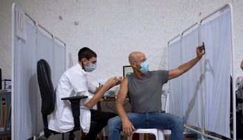 An Israeli man takes a selfie while receiving the third Pfizer-BioNTech COVID-19 vaccine in Ramat Gan, Israel, last month.