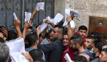 Palestinian men gather in front of the chamber of commerce in Jabalya in the Gaza Strip on Wednesday in the hopes of obtaining an Israeli work permit.