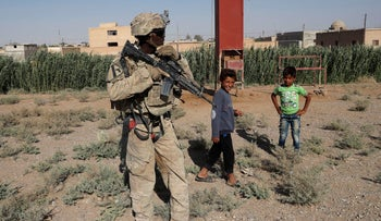 A U.S. soldier stands near Syrian children on a road to Raqqa, Syria, 2017