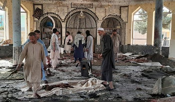 People view the damage inside a mosque following a bombing in Kunduz, province northern Afghanistan, on Thursday.