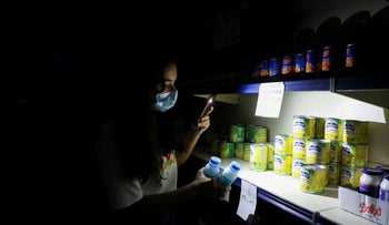 A customer uses her phone's flashlight in a store during a power cut near Bhamdoun, Lebanon, today.
