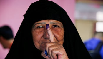An Iraqi woman shows her ink-stained finger after casting her vote at a polling station during the parliamentary election in the Sadr city district of Baghdad, Iraq, today.