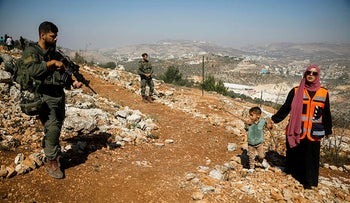 A boy looks at Israeli soldiers during a protest in support of Palestinian farmers and against Israeli settlements, in Beita, West Bank, today.