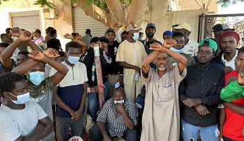 Migrants gesture as they wait outside the United Nations High Commissioner for Refugees (UNHCR) negotiation office in Tripoli, Libya, today.
