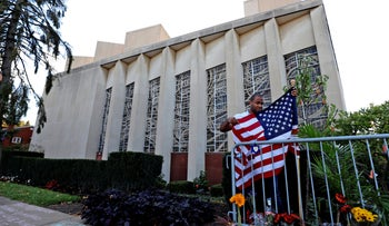 A man places an American flag outside the Tree of Life synagogue in Pittsburgh on the first anniversary of the shooting at the synagogue, 2019.