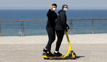 Two men on a scooter riding along the promenade in Tel Aviv while wearing face masks.