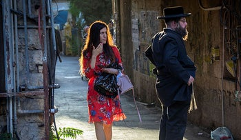 A woman standing next to an ultra-orthodox man, Israel, 2021.