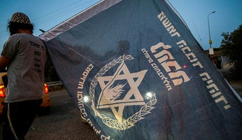 An Israeli holds a flag belonging to the far-right, anti-Arab Lehava organization during a protest in the West Bank, 2019.