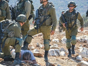 Israeli soldiers detaining Mohammed al-Khatib, who had come with others to harvest olives, near Salfit in the West Bank.