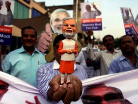 A supporter of the Hindu nationalist Bharatiya Janata Party in Ahmadabad, India holds a statue of Narendra Modi after he was announced as the party's candidate for prime minister in 2013