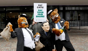 Robin Hood Tax campaigners pose for photographers dressed as fat cats and Britain's Chancellor of the Exchequer George Osborne outside the HSBC annual general meeting at the Queen Elizabeth II conference centre in London, Friday, April 22, 2016. (AP Photo/Matt Dunham)