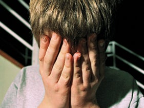 Child hiding face in illustrative photo of child abuse.