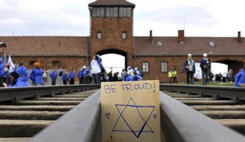 A plaque is placed by March of the Living participants on railway tracks at Auschwitz near Oswiecim, Poland, May 2, 2011.