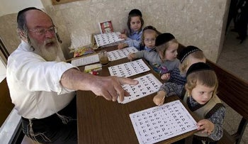 Ultra-Orthodox children sit in front of a teacher as they learn the alphabet at the Shomrei HaHoma Torah School for boys in Jerusalem. Nov. 9, 2010.