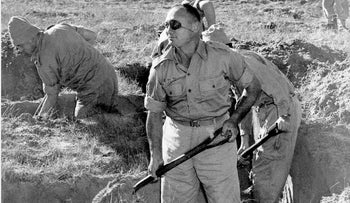 Maj. Gen. Moshe Dayan in digs a trench in the Gaza Strip in 1956.
