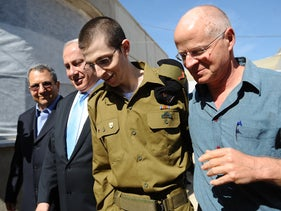 Defense Minister Ehud Barak, Prime Minister Benjamin Netanyahu, IDF Soldier Gilad Shalit and his father, Noam Shalit, after landing at Tel Nof Air Base, Oct. 18, 2011.