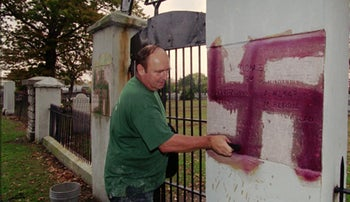 Archive: A man removing a spray-painted swastika from the gate of a Jewish cemetery.