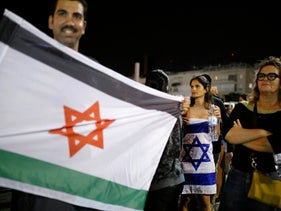 A protester holds a flag, designed like an Israeli flag with the Palestinian national colors, as he demonstrates against new austerity measures set to be included in Israel's 2013-2014 budget.