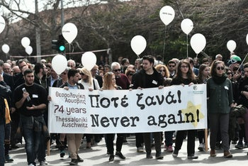 People walk in Thessaloniki during a commemoration ceremony marking the departure of the first train from the northern Greek city to the Auschwitz concentration camp on March 15, 1943, on March 19, 2017