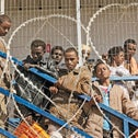 African migrants behind barbed wire at the Saharonim detention facility in the Negev, 2012.