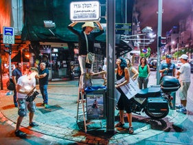Protesters pasting names of Sephardi Jews on Israeli street signs, June 9, 2013.