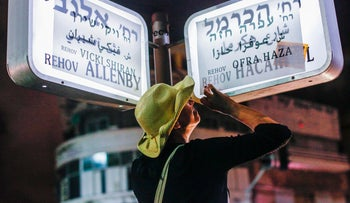 Protesters pasting names of Mizrahi Jews on Tel Aviv street signs on June 9, 2013.