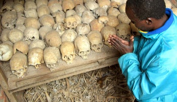 A Rwandan survivor of the 1994 Genocide prays over the bones of genocide victims at a mass grave in Nyamata, Rwanda Tuesday, April 6, 2004.
