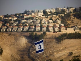 An Israeli flag is seen in front of the West Bank Jewish settlement of Ma'aleh Adumim.