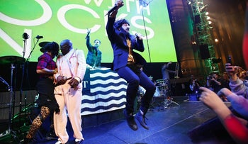 Macklemore jumping up and down in costume during a performance at the EMP Museum in Seattle on May 16, 2014.