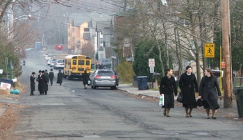 Young women walk on the designated women's side of the street in New Square, a Hasidic village in suburban New York.