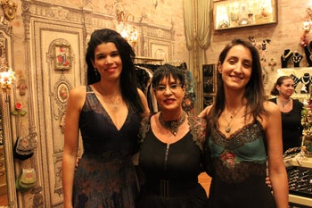 Michal Negrin at a store opening, flanked by Moran Mazig, left, and Tal Shapsa, demonstrating the clothes, August 2013