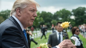 Trump receives a flower from a woman as he visits Arlington National Cemetery to mark Memorial Day, Virginia, May 29, 2017.