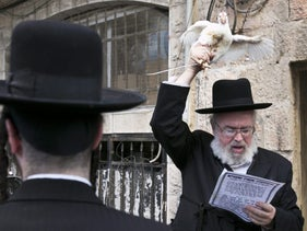 A man practices the kapparot ritual in Jerusalem, 2012.