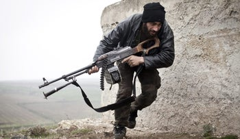 A Free Syrian Army fighter takes cover during fighting with the Syrian Army in Azaz, Syria in 2012.
