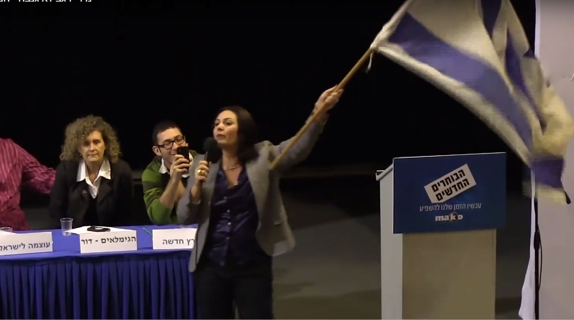 Miri Regev, now minister of culture and sport, waving the flag at a women's panel.