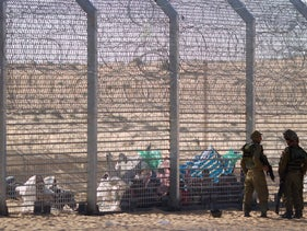 African refugees sit on the ground behind a border fence after they attempted to cross illegally from Egypt into Israel as Israeli soldiers stand guard.
