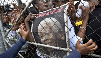 A poster of Nelson Mandela is seen behind a metal gate, December 11, 2013.
